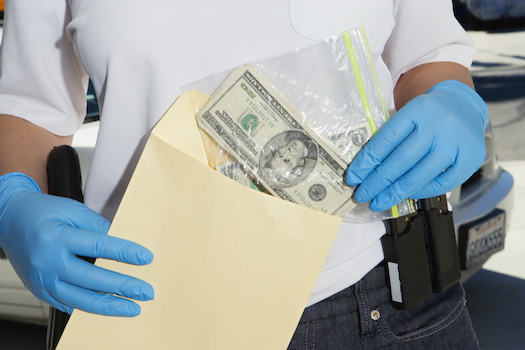 Police Officer Putting Money Away